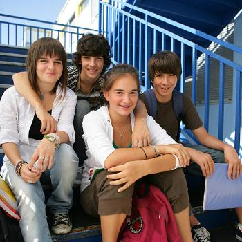 Adolescents souriants assis sur les marches. / © Fotolia
