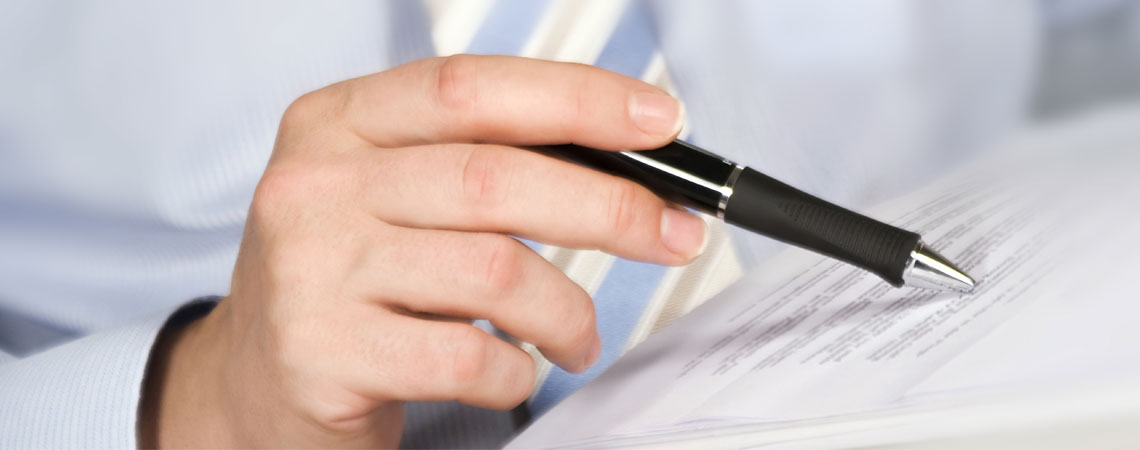 Main tenant un stylo pour relire un document. / ©PhotoSG - stock.adobe.com